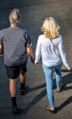 Hiking elderly couple holding hands and walking on the street and breathing healthy fresh air to strengthen immunity and strengthen the body and enjoying the fellowship