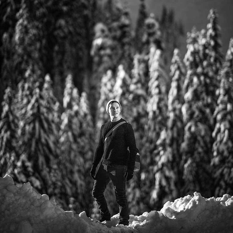 Man holding Leather Bag product photo in Snowy mountains and trees