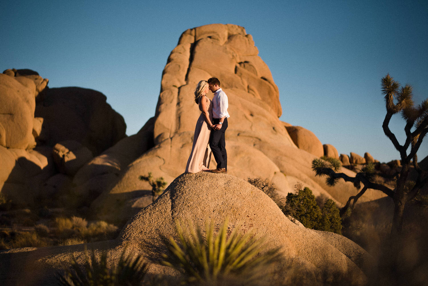 Couple standing on rock in desert at sunset