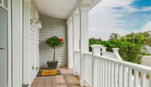 Front porch with paint-free trim and railings complimented with cedar shingles.