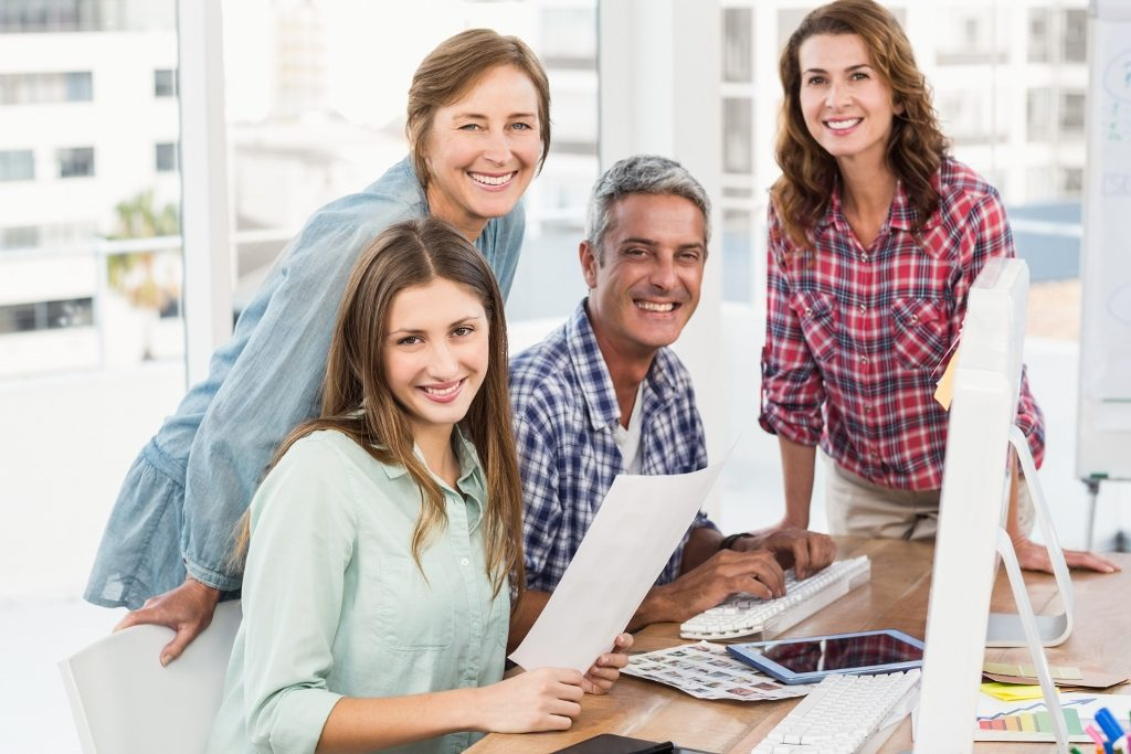 Four casual colleagues using computer