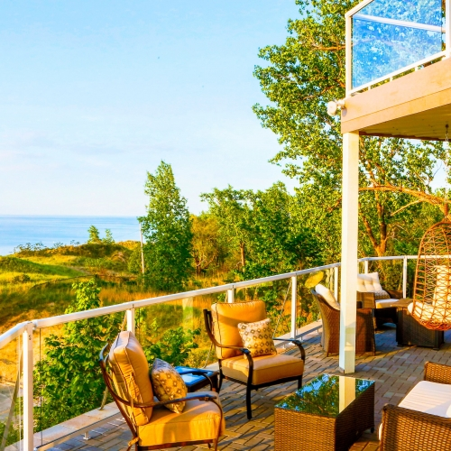 An outdoor patio filled with comfortable furniture, beyond the patio is a view of the bright blue water of Lake Michigan and the Indiana Dunes National Lakeshore.