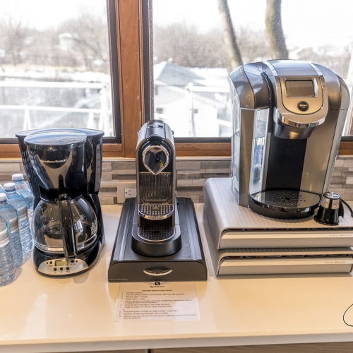 Four different models of coffee makers on top of a white counter next to a small group of plastic water bottles.