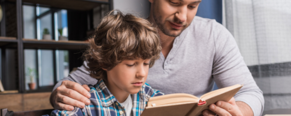 A father helps his son with reading comprehension.