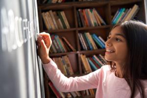 A girl spelling words on a blackboard.