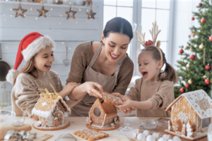 Mother and two daughters enjoy the holiday season by decorating gingerbread houses
