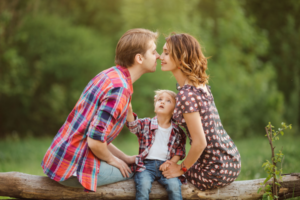 A couple kisses at a park while their young son sits between them.