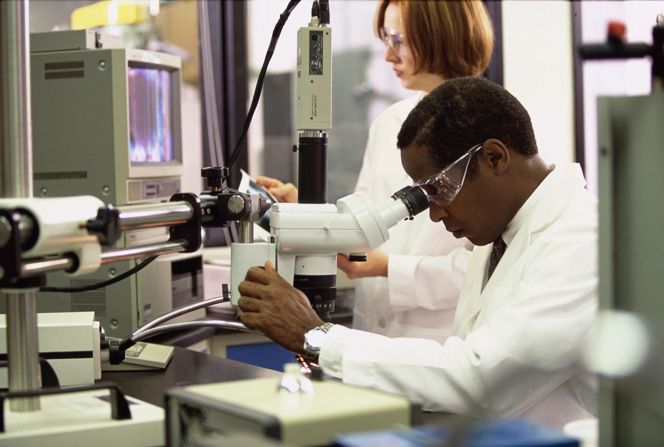 A black male scientist looking in a microscope in a lab with a white female scientist in the background