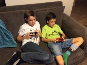 two boys playing video games on the couch