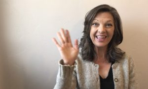 Kristin, a woman with brown hair, is smiling and waving in front of a white wall with a sweater and black shirt