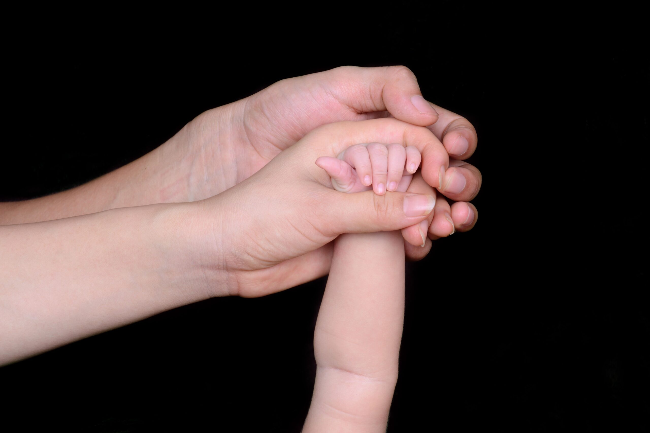 father's hand holding mother's hand holding babies hand