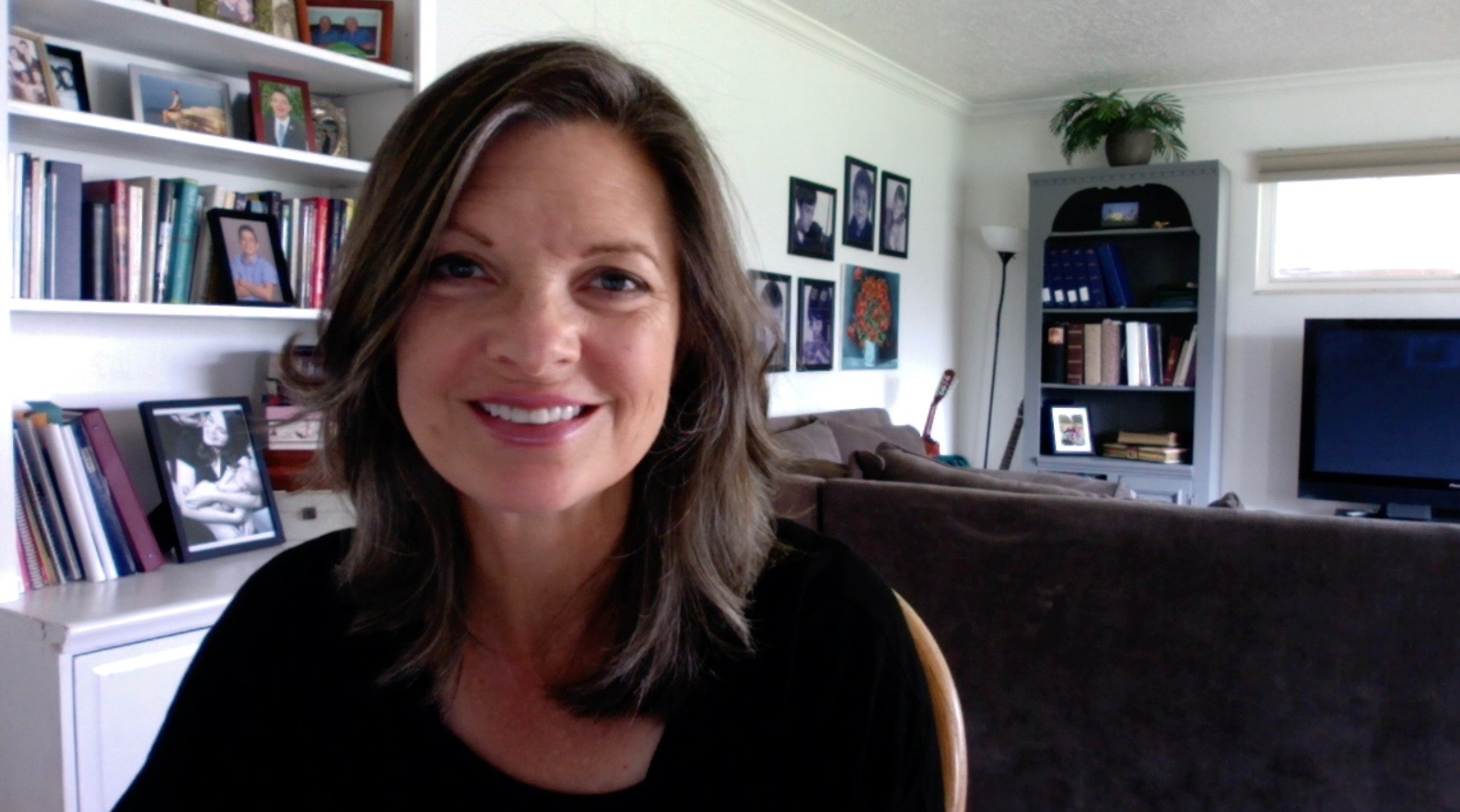 Kristin in her home recording a video with black top on