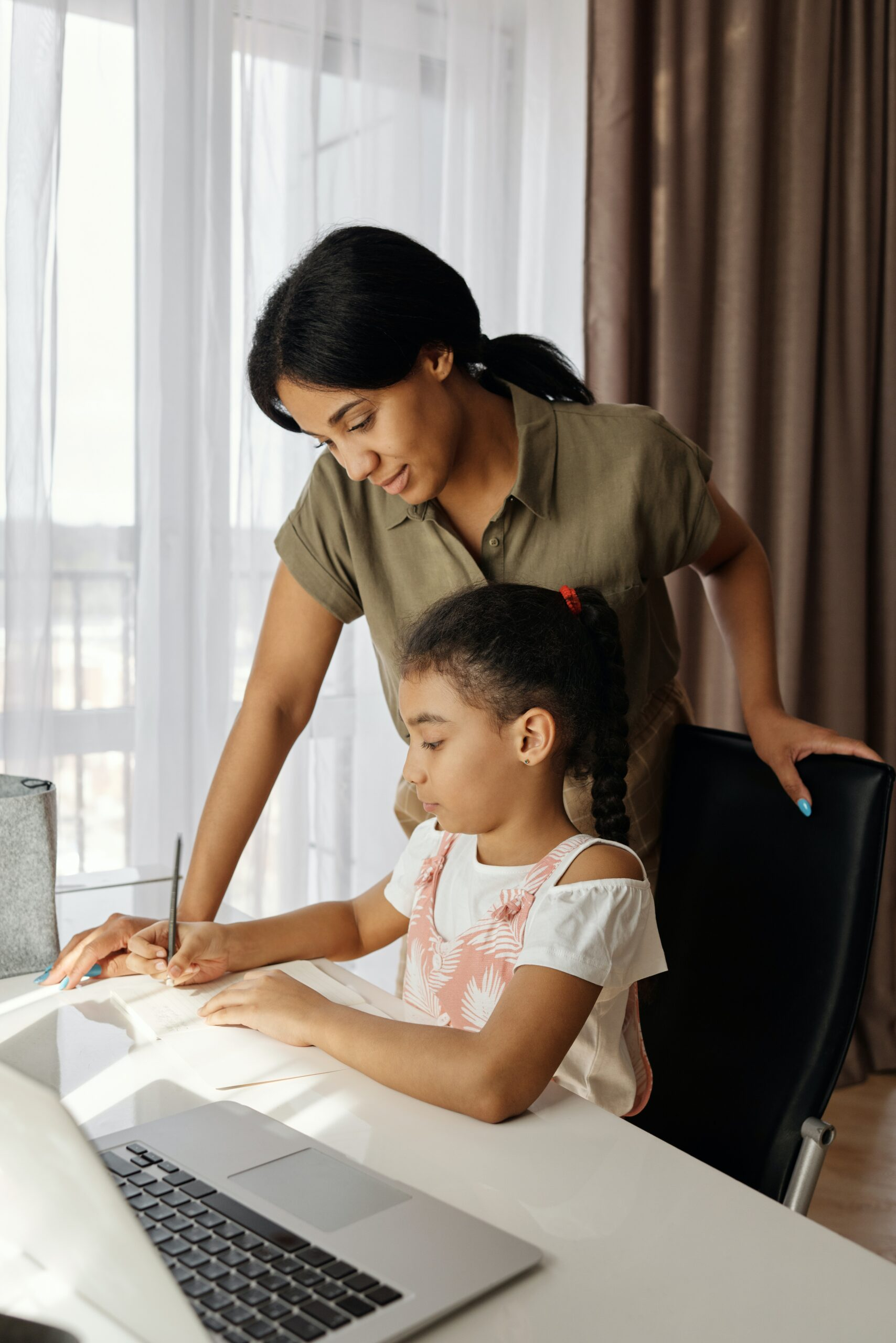 Mother overseeing her daughter at the table, doing her school work with computer open on the table