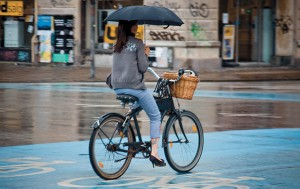 Big Picture: woman cycling whilst holding an umbrella