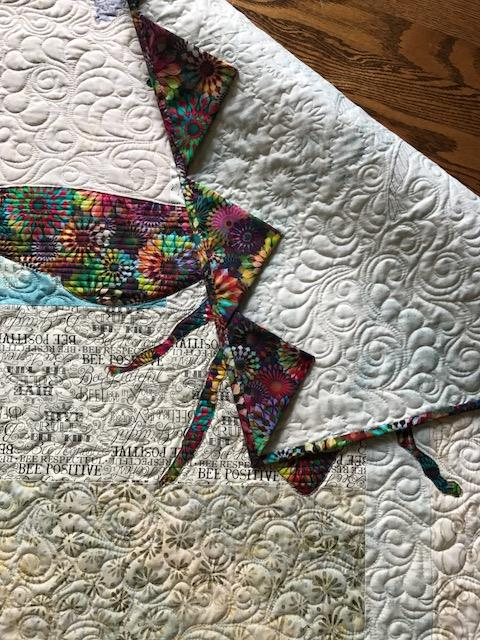 Image of back of quilt with prairie points.