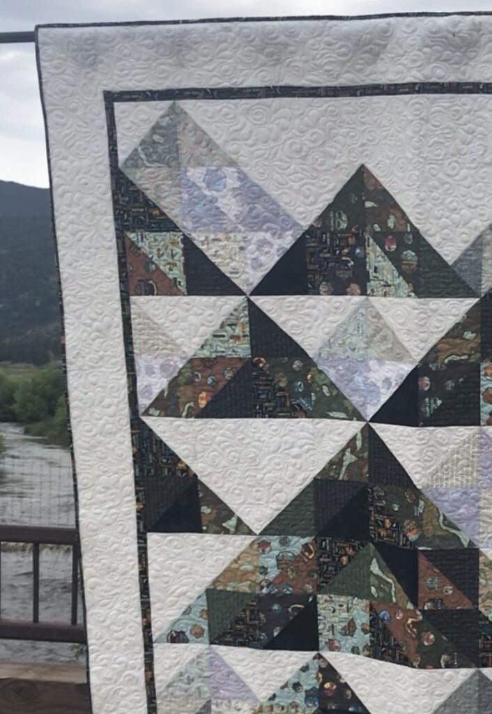 Matt holding the quilt in the mountains.
