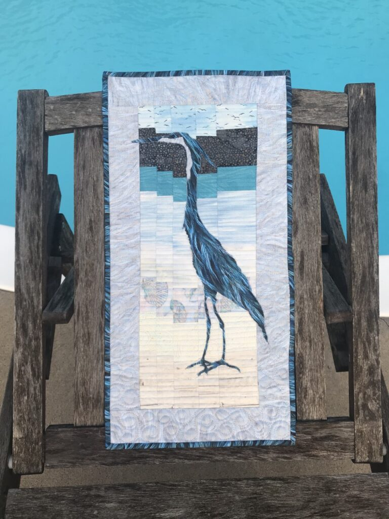 Image of a great blue heron quilt at poolside