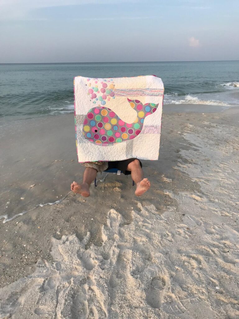 Image of marine saving Bubbles the baby whale quilt at the beach.