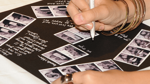 An image of a hand signing a Memory book while holding a copy of the strip