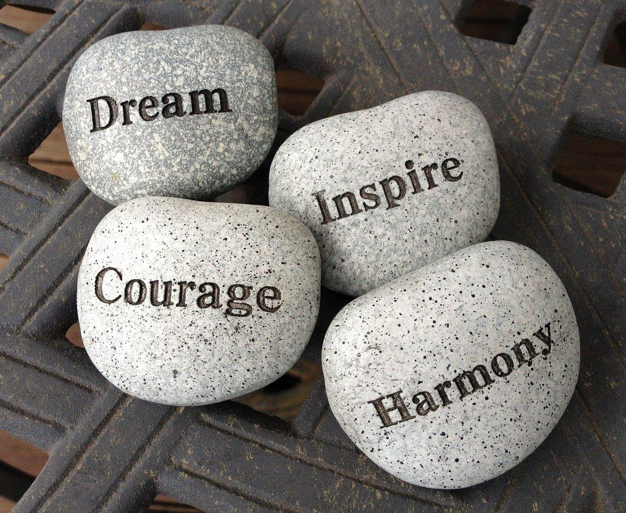 Dream, courage, inspire, harmony written on stones