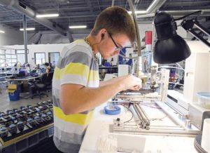 Seth Dykema works on a cycling component at the gluing station at Stages Cycling in Boulder. (Cliff Grassmick)