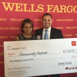 Accepting a donation check from Wells Fargo's Anthony Rosado.