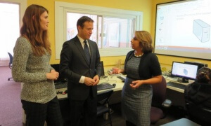 Executive Director Nelly Jimenez discusses the digital education center with Comcast executives Janet Steiner and William Bronson.