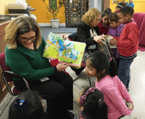 Children listen as Arlete and Jessica read the new books