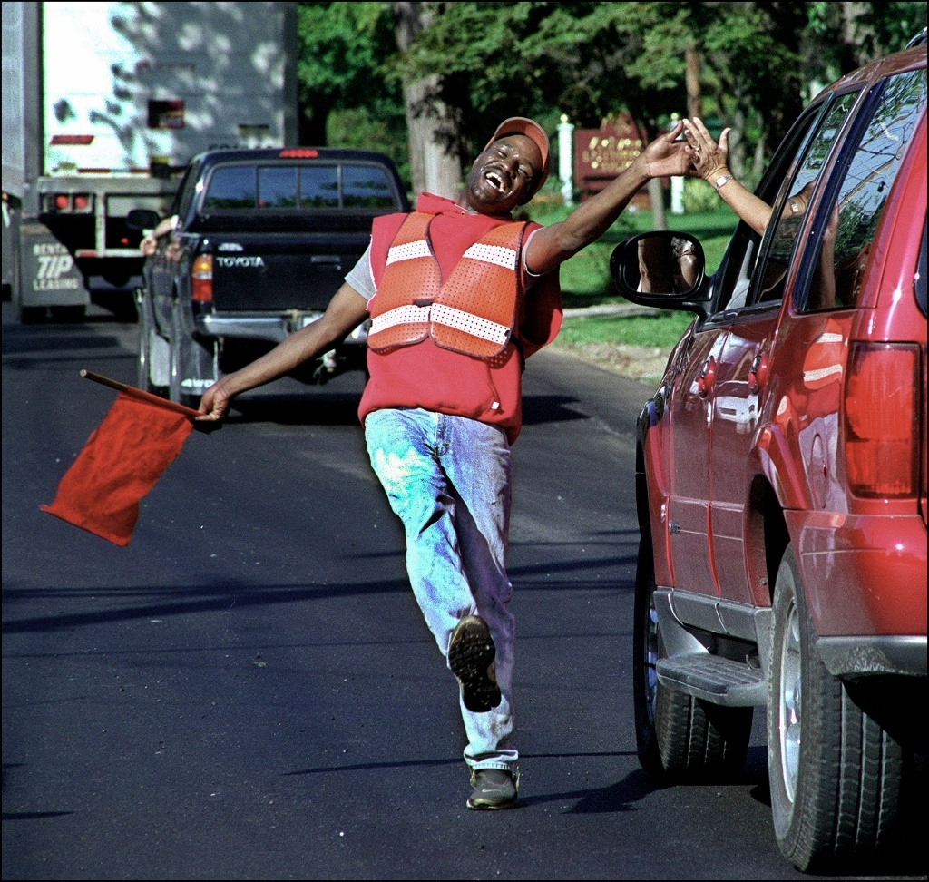 Road crew flagger Anthony Snyder high fives a passing driver