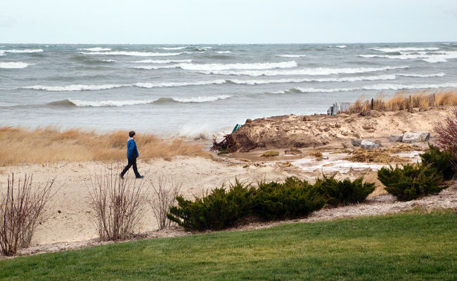 A resident walks along Ipperwash Beach on the shore of Lake Huron. Band members from the Kettle and Stony Point First Nation removed a barricade from Ipperwash Beach last week to allow cars to use the beach as a road to connect Kettle Point to Stony Point native communities, a move that has some residents up in arms. (CRAIG GLOVER, The London Free Press)