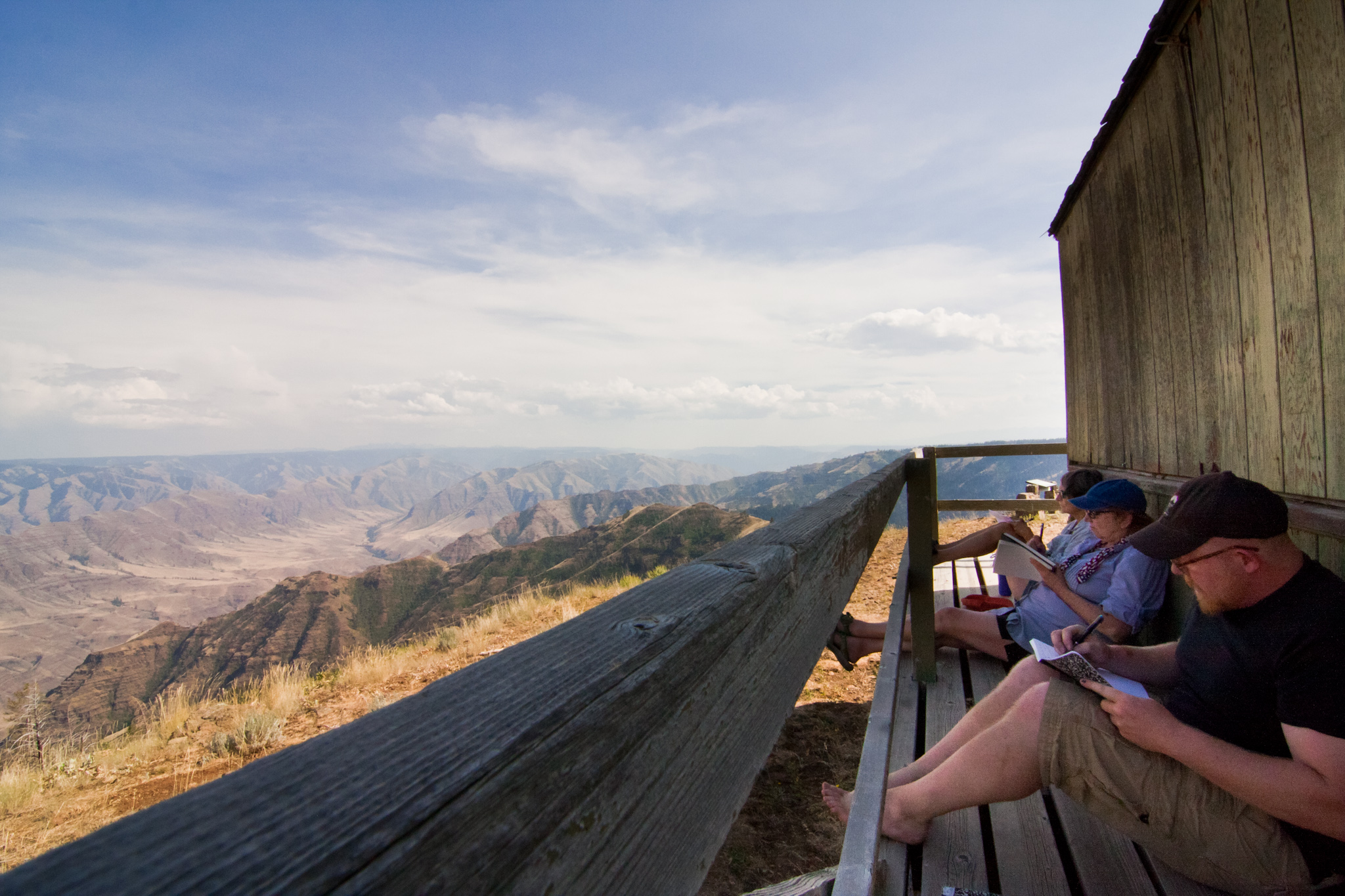 In love with the view and writing in journals, three writers sit on the deck of a fire outlook overlooking Hells Canyon in NE Oregon.