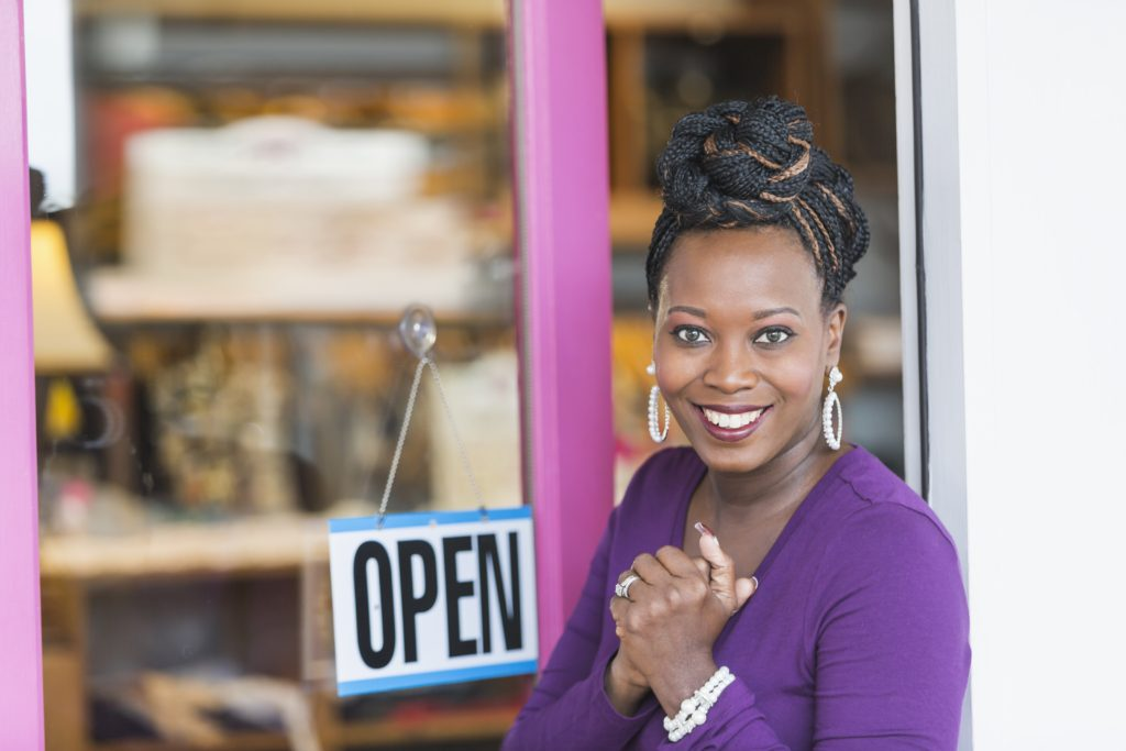 Latin American Women Business Owners with Open Sign