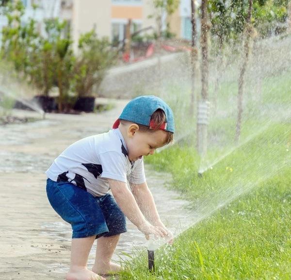Kid playing at the sprinkler
