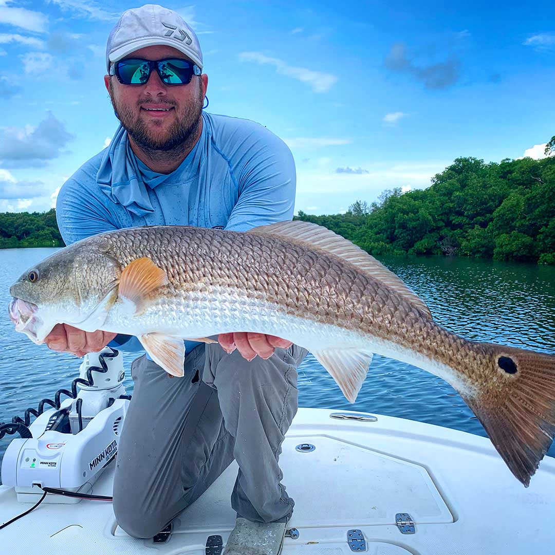 Capt Matt Luttmann with a solid redfish landed during an inshore charter with InshoreAction Charters.