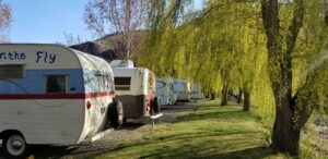 Camp trailers parked along the riverfront at Swiftwater RV Park