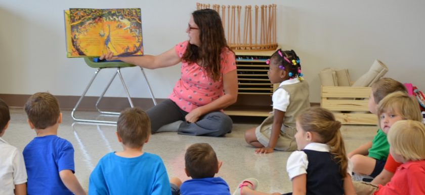 Preschool teacher reads a book to students during line time.