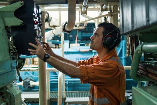 Marine engineer inspecting ship's engine in engine control room