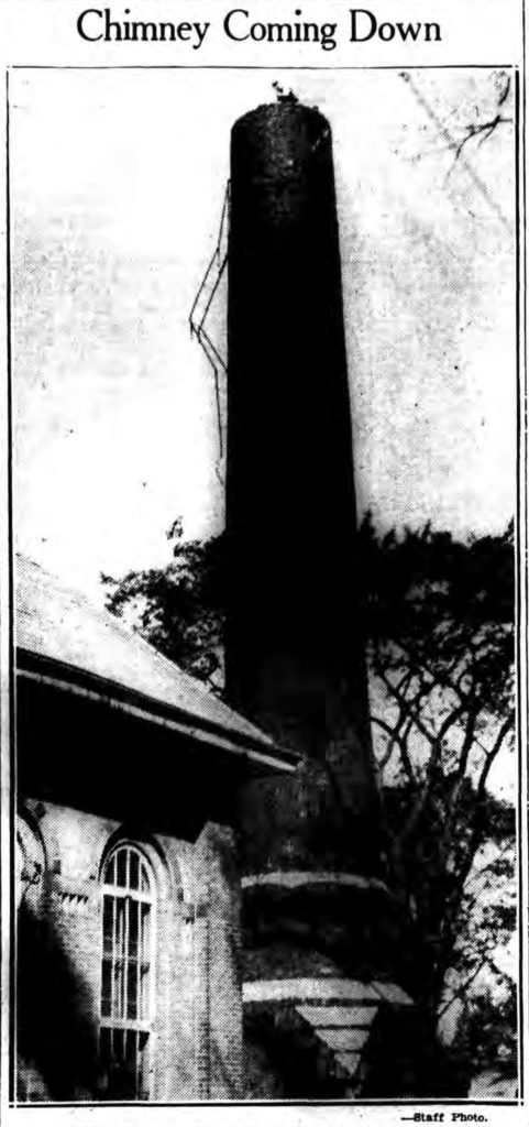 """Ben Fraser, a member of the Department of Public Works, is shown atop the chimney of the Public Bath House on Second Avenue in Lansingburgh as he commenced its destruction.  For a long time the chimney has been in a dangerous condition. """"Chimney Coming Down."""" Times Record. October 8, 1938: 7 cols 3-4. (Staff Photo.) (Cropped from scan by fultonhistory.com)"""