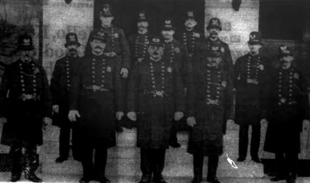 """""""FOURTH PRECINCT POLICE—Above is the Lansingburgh police force as it appeared in the early 1900s, a few years after Lansingburgh became a part of Troy.  The picture was taken in front of the precinct station house on the east side of Second Avenue between 116th and 117th streets.  Can you name those not identified?  Sgt. Albert D. Chesbrough is in center of front row, Sgt. William M. Flynn, second left, and Ptl. Holman P. Shires at extreme left.  Between Flynn and Shires on the step is Ptl. Samuel E. Rounds.  Behind Flynn is Ptl. James O'Brien who later became captain of the precinct.  The officer standing behind Sergeant Chesbrough's left shoulder is Ptl. Louis Hansen.  The man, front row, second right is believed to be Ptl. Daniel Bird, and between him and the officer on extreme right is either Ptl. Joseph Schultz, who also later captained the precinct, or Ptl. John L. Rabie. (Photo loaned by George MacCulloch)"""" The Record. October 5, 1968: B22."""