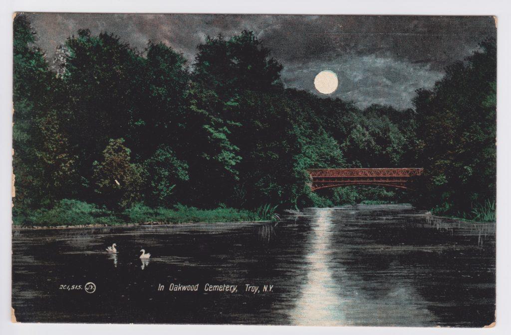 """Color depicting of night scene on Oakwood Cemetery's round lake or """"Ullswater"""" crossed by metal bridge"""