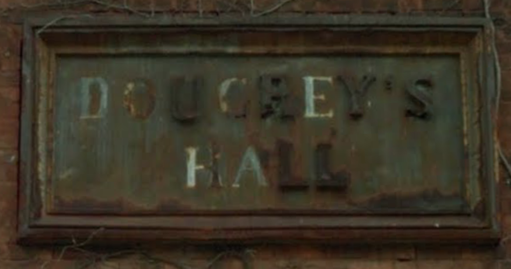 The sign, a worn, greenish color, on the brick wall of the building, framed by something like a picture frame, has white paint or glue indicates most of the letters; only U R Y ' S L L have raised brownish letters remaining.