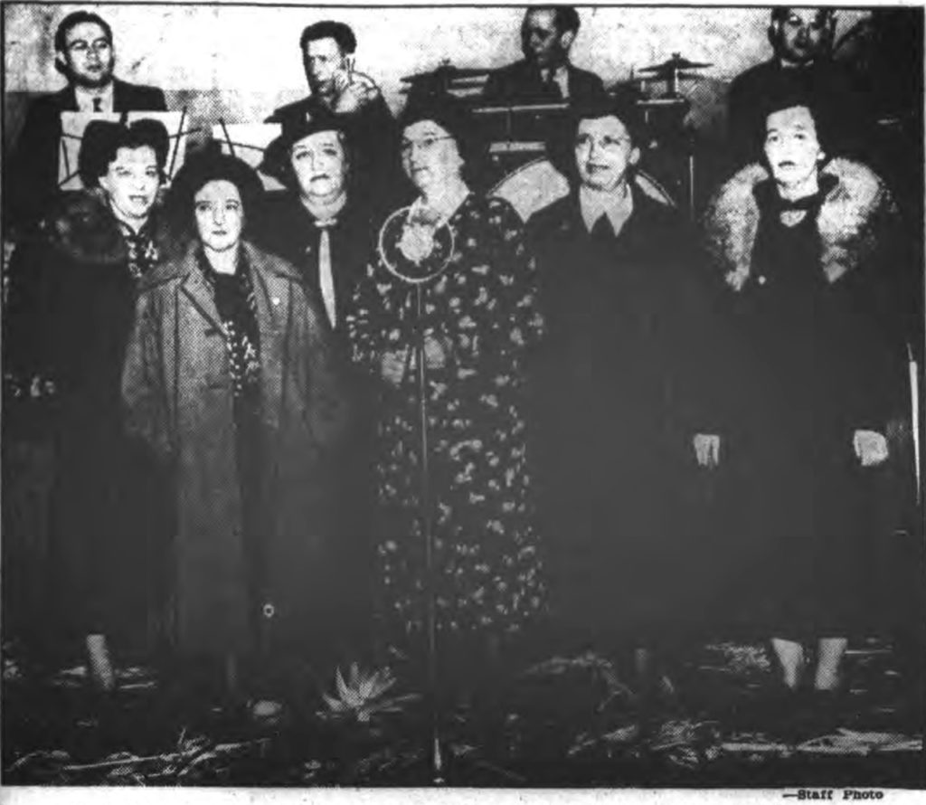 Behind and above the women named, who were pictured standing in front of a microphone, were five male members of a band or orchestra seated on a stage with sheet music before them.