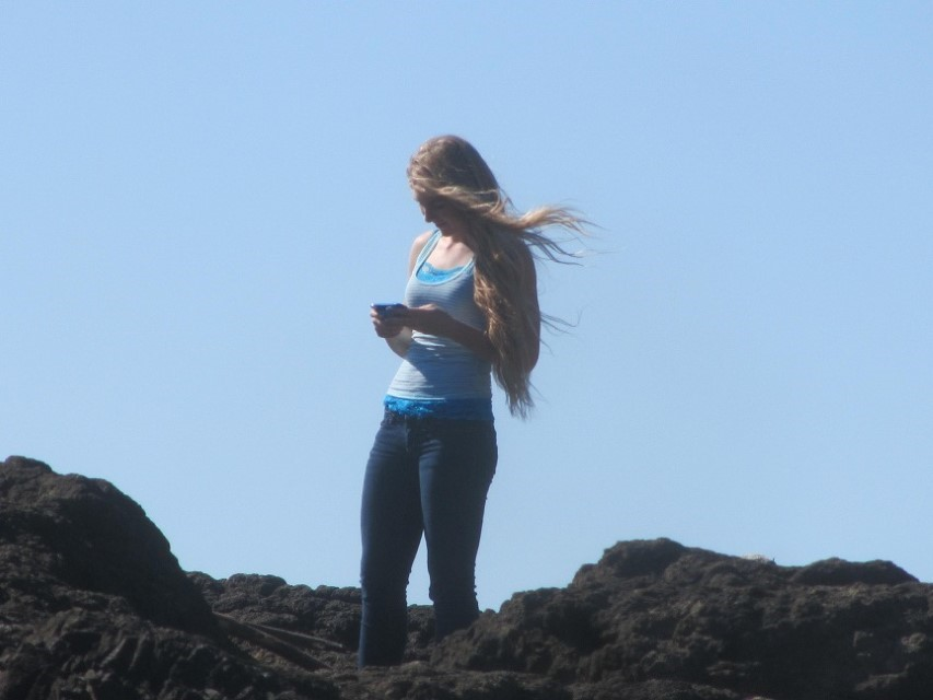 What does Holly do when at the beach looking for tide pools? She texts her friends of course.