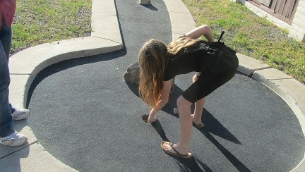 Sarah gets out after school, and learns to putt