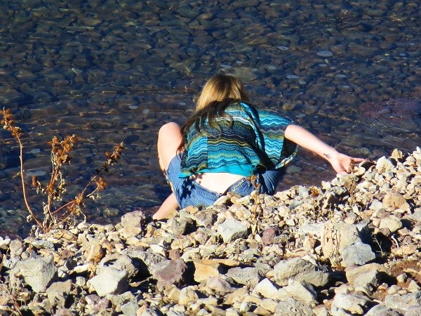 Sarah is checking the water temperature of the lake.