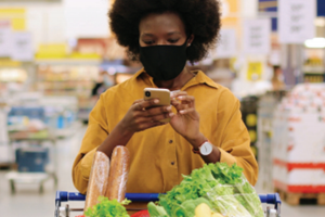 African-American woman shopping for groceries while using her cell phone
