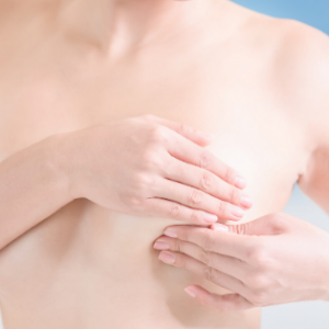 Image of woman feeling for a breast lump wondering what to do when she finds a breast lump