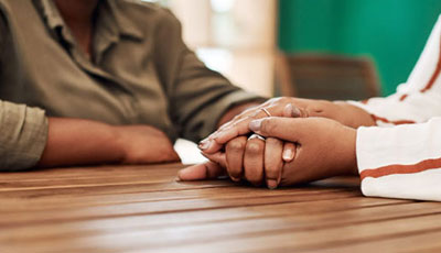 Person holding someones hand on top of a table