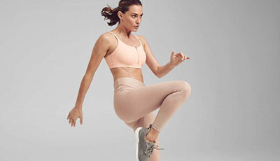 EverViolet Model wearing a sports bra and leggings with her knee up mid-move