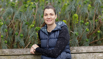 Anne Peled, MD sitting outside on a park bench with tall green plants in the background